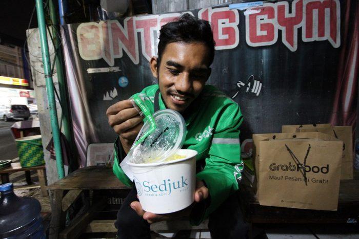 Mitra Pengemudi Grab tengah menikmati paket makanan dari mitra merchant GrabFood